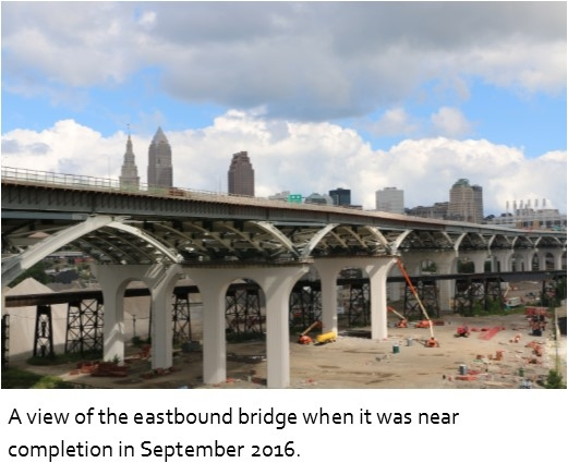 A view of the eastbound George V. Voinovich bridge with construction materials and Cleveland skyline