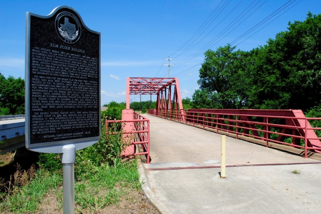 The image shows a historic bridge that allows bicyclists and pedestrians to cross the Elm Fork of the Trinity River. It also is located within the right of way of FM 428, which is slated for expansion. FM 428 is seen in the left of the photo.